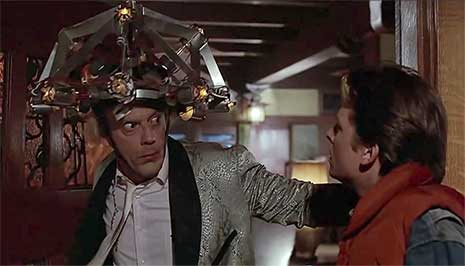 """O incrível e maluco Dr. Emmett Brown (Christopher Lloyd, à esquerda) tenta usar uma invenção em Marty McFly (Michael J. Fox), no filme """"De Volta para o Futuro"""" – Imagem: divulgação"""